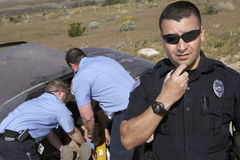 Police Officer With Paramedics Rescuing Car Accident Victim. Portrait of a police officer communicating on radio with male paramedics rescuing car accident Stock Image