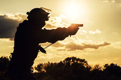 Police officer with pistol. Silhouette of police officer with pistol at sunset Stock Photos