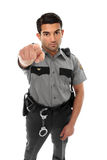 Police officer or prison guard pointing his finger. A police officer, prison guard or similar uniformed man stands firm with pointed finger.  Concept Royalty Free Stock Photography