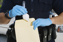 Police Officer Putting Cocaine In Evidence Envelope Royalty Free Stock Photo