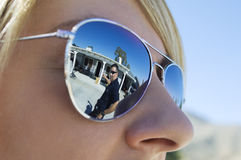 Police Officer Reflected in Sunglasses. Closeup of a police officer's reflection on sunglasses of coworker Royalty Free Stock Images
