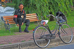 Police officer is resting on a bench in Bangkok, Thailand Royalty Free Stock Image