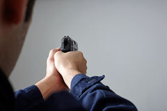 Police officer`s hands aiming with gun. Closeup view of police officer`s hands aiming with gun Stock Images