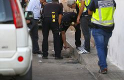 Anti drug raid in mallorca details. A police officer search on the street sewage during an anti drug raid in the la soledat square in palma de mallorca city stock photography