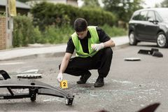 Police officer securing accident scene. Image of police officer securing car accident scene Royalty Free Stock Image