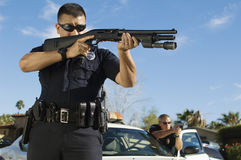 Police Officer With Shotgun. By patrol car Stock Photography