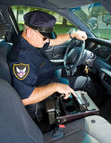 Police Officer With Siren. Police officer using the control panel in his squad car to turn on the lights and siren Stock Photography