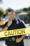 Police Officer Standing Behind Caution Tape. Closeup of a caution tape with male police officer in the background Stock Image