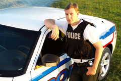 Police officer standing by his car looks directly at camera Stock Images