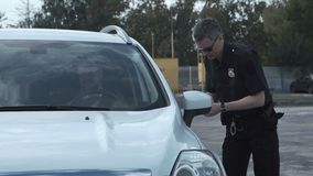 Police officer stopping the driver of a vehicle stock video footage