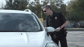 Police officer stopping the driver of a vehicle. And questioning him over an alleged offence through the open window of the car Royalty Free Stock Photos