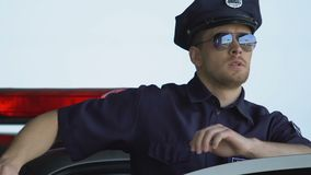 Police officer in sunglasses getting out of car, providing security on streets. Stock footage stock video footage