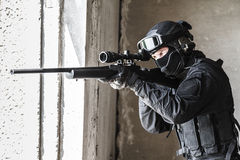 Police officer SWAT in action. Swat police operator with sniper rifle in action blaсk uniforms aiming criminals terrorists from the window stock image