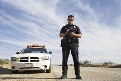 Police Officer Taking Notes In Front Of Car. Full length of a police officer writing on clipboard while standing in front of patrol car Royalty Free Stock Photography