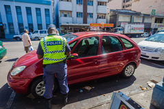 Police Officer Ticket Car. Police officer giving ticket to red car vehicle in the Grey Street Area of Durban Stock Images