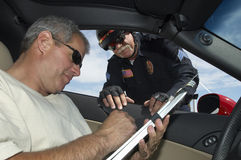 Police officer watching driver sign papers. Police officer looking at men in car signing papers Stock Photo
