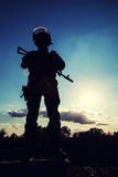 Police officer with weapons. Silhouette of police officer with weapons at sunset Stock Image