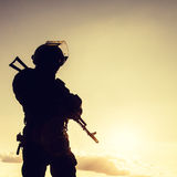 Police officer with weapons. Silhouette of police officer with weapons at sunset Royalty Free Stock Image