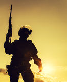 Police officer with weapons. Silhouette of police officer with weapons at sunset Royalty Free Stock Images