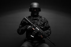 Police officer with weapons. Spec ops police officer SWAT in black uniform studio Royalty Free Stock Photography