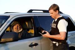 Police officer writing man ticket Royalty Free Stock Image