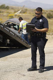 Police Officer Writing Notes At Car Crash Scene royalty free stock image