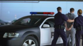 Police officers arresting criminal, wearing handcuffs and putting him in car. Stock footage stock video