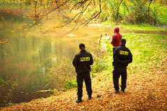 Police officers checking fisherman autumnal park. Fishing inspection. Stock Photos