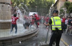 Police officers controlling Mallorca soccer fans celebrations. Local police officers control while Mallorca soccer team supporters celebrate on a fountain Royalty Free Stock Image