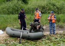 Police officers draw up a protocol for the man for poaching on the Oka River. RYAZAN, RUSSIA - JUNE 16, 2015: Police officers draw up a protocol for the man for Stock Images