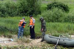 Police officers draw up a protocol for the man for poaching on the Oka River. RYAZAN, RUSSIA - JUNE 16, 2015: Police officers draw up a protocol for the man for Royalty Free Stock Photo