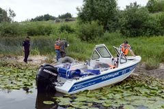 Police officers draw up a protocol for poaching on the river. RYAZAN, RUSSIA - JUNE 16, 2015: Police officers draw up a protocol for poaching on the river Stock Image