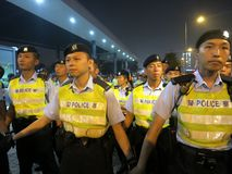 Chinese Police Officers Hold Back Crowd at a Prote. HONG KONG - NOV. 6, 2013: Hong Kong police officers make a human wall at a demonstration in Hong Kong Stock Photography