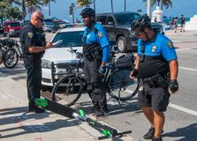 Police officers investigate a motor scooter accident on a street. Ft Lauderdale, Florida - May 4, 2019: Police officers investigate an electric motor scooter royalty free stock photos