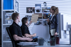 Police officers searching files. Horizontal view of police officers searching files Royalty Free Stock Image
