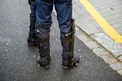 Police officers securing the zone in front of Yellow Jackets Gil. Police baton on right feet of a French police officer at Yellow jackets protest in French city stock photo