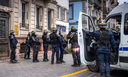 Police officers securing the zone in front of Yellow Jackets Gil. STRASBOURG, FRANCE - DEC 8, 2018: Rear view of police officers securing the zone in front of royalty free stock photos