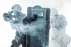 Police officers SWAT. Studio shot of swat police special forces aiming criminals with rifle pistol hiding behind ballistic shield and smokescreen. Isolated on Royalty Free Stock Images