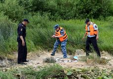 Police officers take out fish from a fisherman for poaching on the Oka River. RYAZAN, RUSSIA - JUNE 16, 2015: Police officers take out fish from a fisherman for Royalty Free Stock Photography