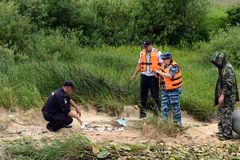 Police officers take out fish from a fisherman for poaching on the Oka River. RYAZAN, RUSSIA - JUNE 16, 2015: Police officers take out fish from a fisherman for Stock Images