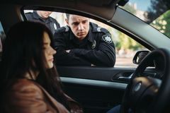 Police officers in uniform check female driver. Male police officers in uniform check female driver on the road. Law protection, car traffic inspector, safety royalty free stock image