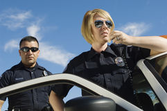 Police Officers Using Two-Way Radio. Female police officer using two-way radio with coworker standing by patrol car Royalty Free Stock Photo