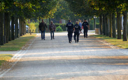 Police officers walk next to people in park walking zone Royalty Free Stock Photo