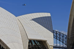 Police Over Sydney Landmarks. A police helicopter hovers in the sky over two of Sydney's most recognizable landmarks - The Sydney Harbour Bridge and the Sydney Royalty Free Stock Photos