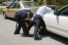 Police Pat Down. Uniformed police officer patting down a suspect pulled over during a traffic stop Royalty Free Stock Photo