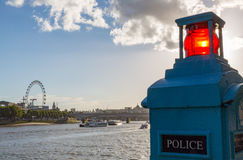 Police phone box on the Thames with London Eye Stock Photography