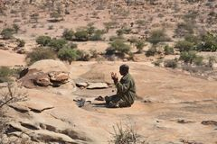 Police pray. LAS GIL, SOMALIA - JANUARY 9, 2010: Complex of caves with petroglyphs is the most significant monument of the epoch of the neolith in Africa,its Stock Photos