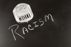 Police Profiling. The word RACISM on a chalkboard with a police badge Stock Photo