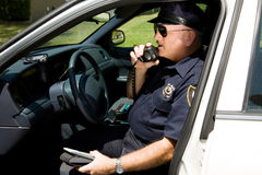 Police - Radioing In. Police officer in squad car, radioing in to headquarters Royalty Free Stock Photo