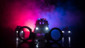Closed handcuffs on the street pavement at night with police car lights. Police raid at night and you are under arrest concept. Silhouette of handcuffs with stock photo